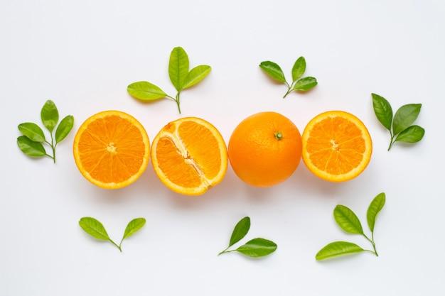 Hohes vitamin c. frische orange zitrusfrucht mit den blättern getrennt auf weiß.