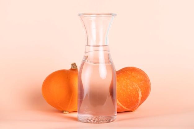 Hohes wasserglas, umgeben von kürbissen