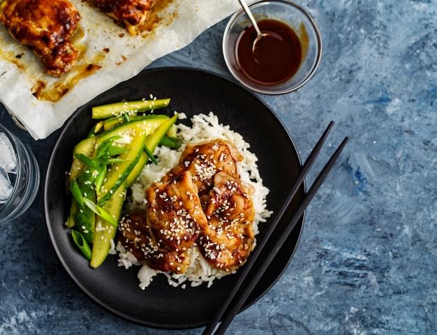 Hoisin huhn. traditionelle asiatische küche. hähnchen mit sauce, reis und eingelegten gurken.