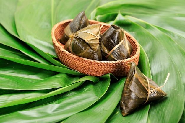 Hokkian reisknödel zongzi, bakcang oder bacang. traditionelles chinesisches essen auf grünem blatt-bambushintergrund des drachenboot-festivals, duanwu-festival. designkonzept für werbung.