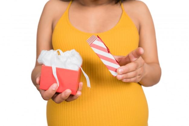 Holding der schwangeren frau und öffnende geschenkbox.