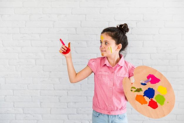 Holdingpalette des kleinen mädchens, die etwas mit dem gemalten roten finger zeigt