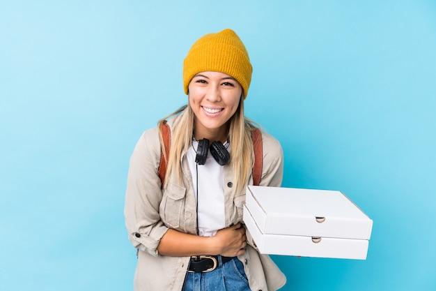 Holdingpizzas der jungen frau, die spaß lachen und haben.