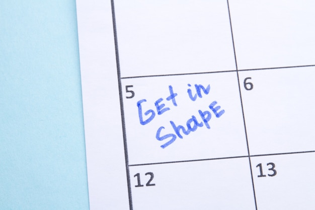 Holen sie sich eine formerinnerung, die mit einem blauen marker in einen kalender geschrieben wird und planen, sportübungen zu machen, um...