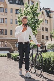 Holen sie sich einen beschäftigten jungen braunhaarigen mann, der mit einem fahrrad im park steht und anschaut Premium Fotos