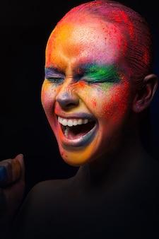 Holi farben festival. porträt des glücklichen lachenden mode-mädchens mit buntem puder-make-up. schönheitsmodell mit hellem regenbogen-make-up.
