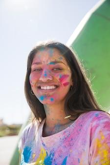 Holi-farbpulver über dem lächelnden gesicht der jungen frau, das kamera betrachtet