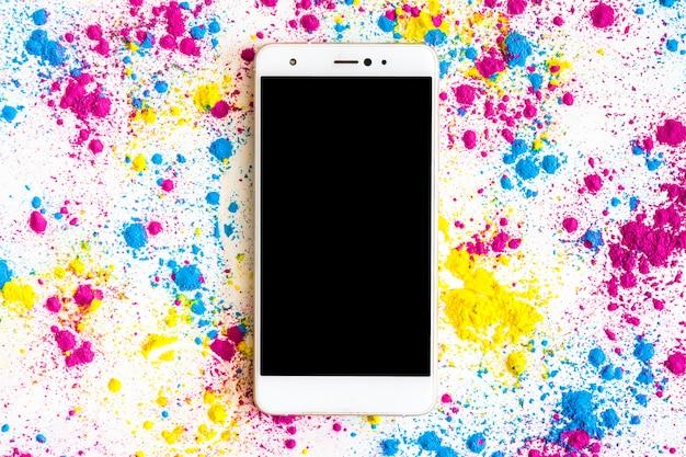Holi-farbpulver um das smartphone mit schwarzer bildschirmanzeige