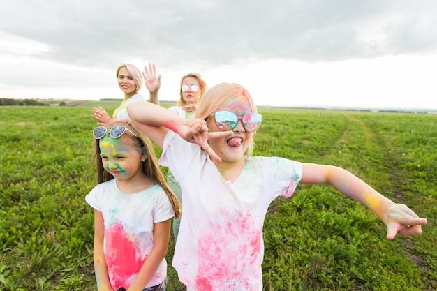 Holi festival, urlaub und glückskonzept - junge teenager und frauen in farben haben spaß im freien