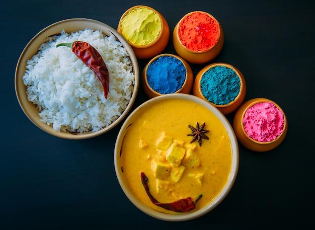 Holi indisches fest der farben. essen mit farben, dampfreis, panir butter masala, pfeffer chili, starnise. pulverfarben über schwarzem hintergrund angeordnet. selektiver fokus