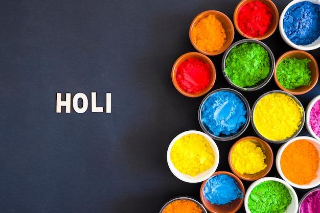 Holi-text nahe den schüsseln des holi-farbpulvers auf schwarzem hintergrund