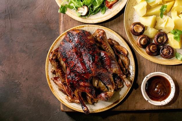 Holiday thanksgiving-tisch mit klassischen gerichten geröstete glasierte ente mit äpfeln, salzkartoffeln, grünem salat und sauce auf dunklem holztisch mit herbstdekor. flach legen, platz kopieren