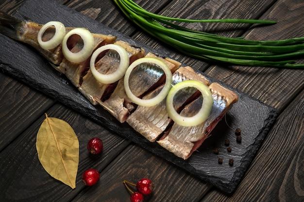 Holländischer roher hering mit zwiebeln und gewürzen auf servierbrett. die idee eines snacks für ein straßencafé oder ein restaurant