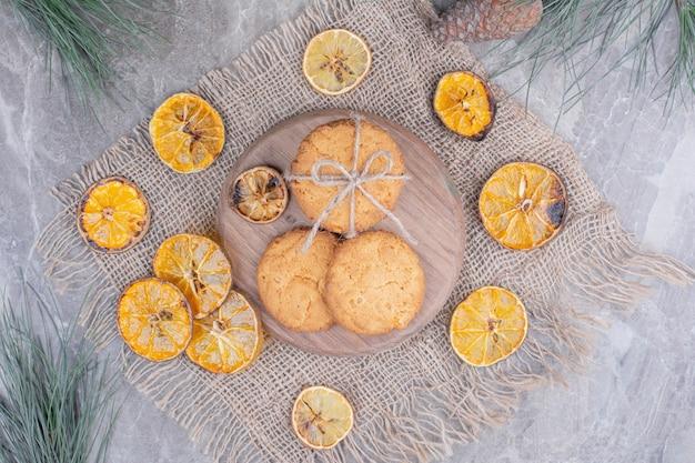 Holland waffeln und kekse auf einem holzbrett mit trockenen orangenscheiben herum.