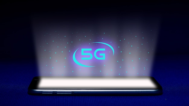 Hologramm von 5g. smartphone und 5g hologrammbild auf blauem hintergrund. das konzept der 5g-technologie ist eine neue generation von netzwerken. - bild