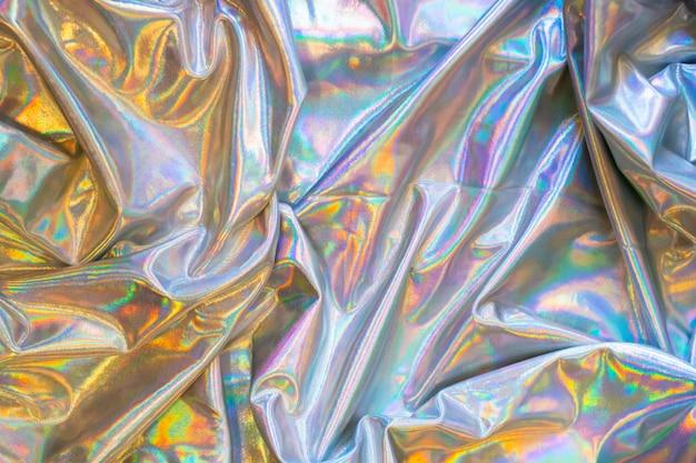 Holographischer schillernder meerjungfrauenfolienbeschaffenheitshintergrund. futuristische neonfarbene trendige silberfarben