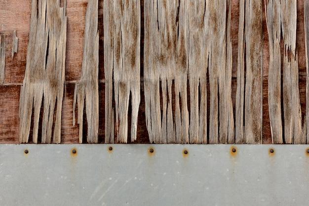 Holz, das auf gealterter oberfläche mit rostigen nägeln abbricht