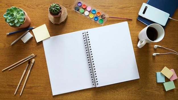 Holz-desktop mit aquarell-malwerkzeugen, einem offenen notizbuch und pinseln