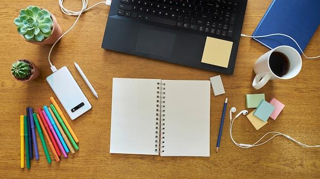 Holz-desktop mit zeichenwerkzeugen wie einem offenen notizbuch und buntstiften
