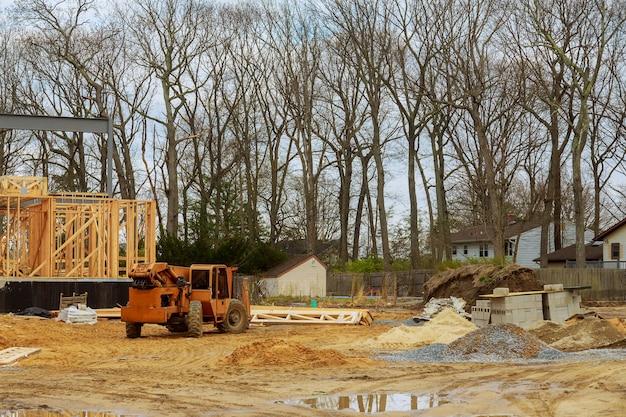 Holz gebäuderahmen auf neuem wohnbauhaus, das einen boom-lkw-gabelstapler im neuen haus einrahmt