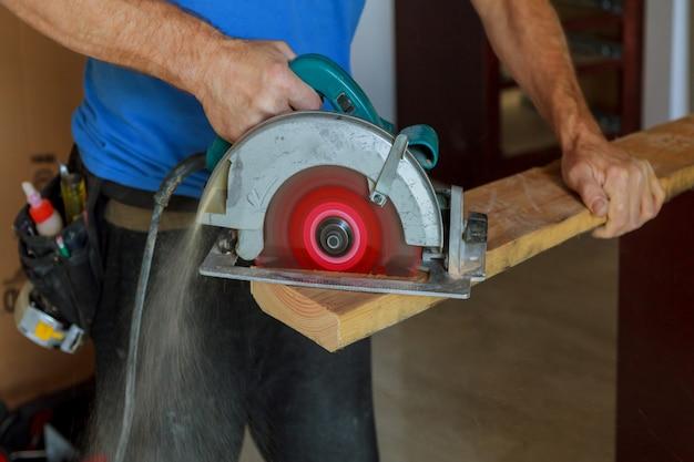 Holz in den gutaussehenden tischler des neuen hauses unter verwendung einer kreissäge installieren, während holz installiert wird