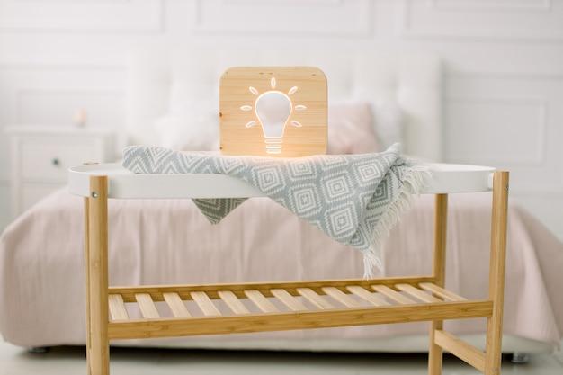 Holz lapms und dekor details zu hause interieur. stilvolle handgemachte holzlampe mit ausgeschnittenem bild der elektrischen glühbirne auf kleinem couchtisch.