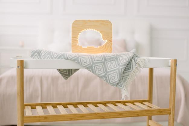 Holz lapms und dekor details zu hause interieur. stilvolle handgemachte holzlampe mit ausgeschnittenem igelbild auf kleinem couchtisch.