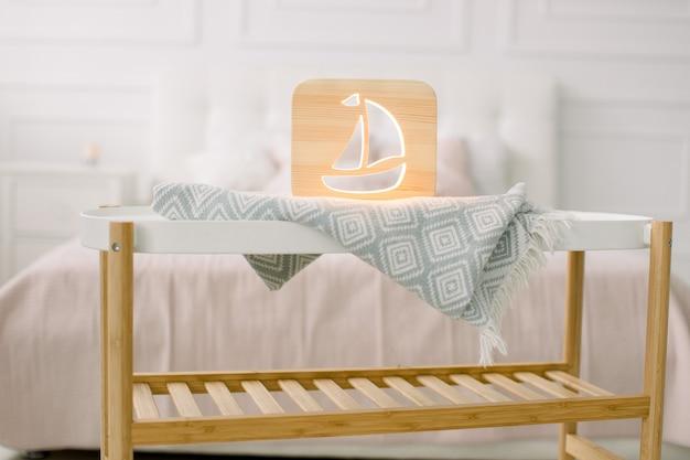 Holz lapms und dekor details zu hause interieur. stilvolle handgemachte holzlampe mit ausgeschnittenem schiffsbild auf kleinem couchtisch.