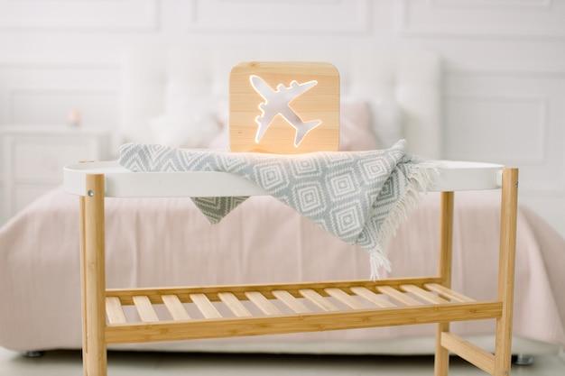 Holz lapms und dekor details zu hause interieur. stilvolle handgemachte holzlampe mit flugzeugausschnittbild auf kleinem couchtisch.