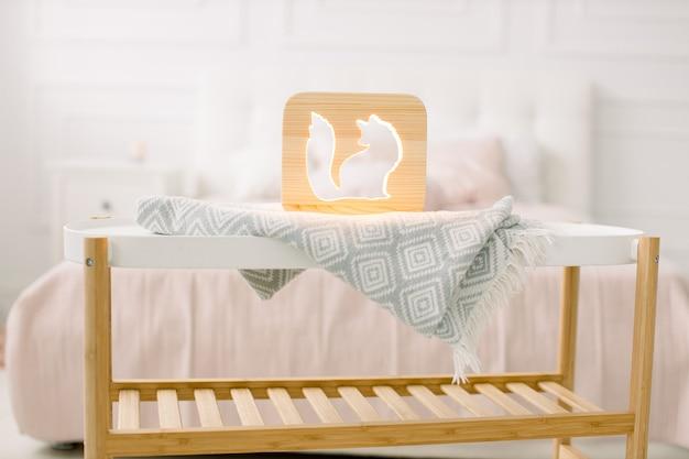 Holz lapms und dekor details zu hause interieur. stilvolle handgemachte holzlampe mit fuchsausschnittbild auf kleinem couchtisch.