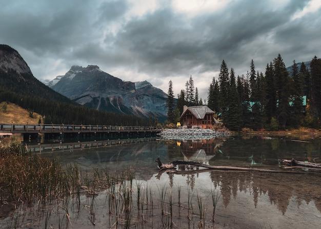 Holz lodge mit rocky mountains reflexion auf emerald lake im yoho national park