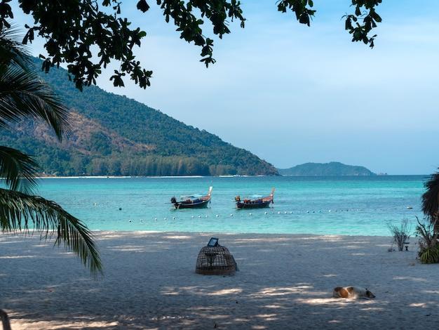 Holz-longtail-boote parken auf blauem meer bei sonnenaufgang strand friedliche aussicht auf das meer szenische entspannungsreise