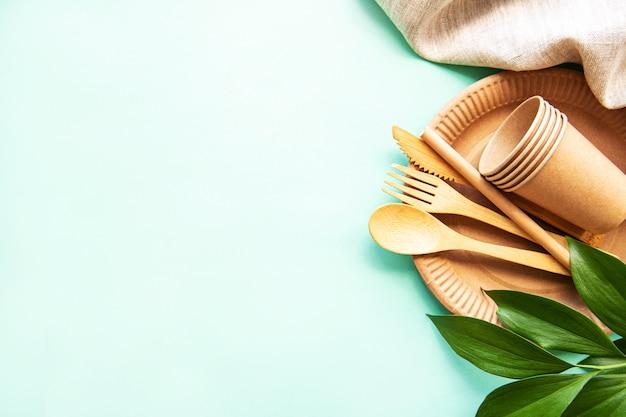 Holz- und papiergeschirr mit grünem exemplar. null-abfall-konzept