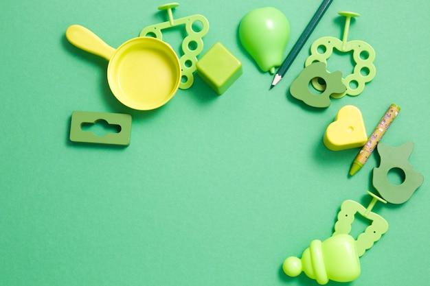 Holz- und plastikspielzeug in verschiedenen grüntönen auf grünem hintergrund, kopierraum, draufsicht, frühe entwicklung, spiele mit kinderkonzept, spielzeug für die kleinen