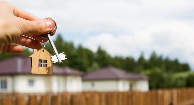 Holzanhänger eines hauses und schlüssel in der hand