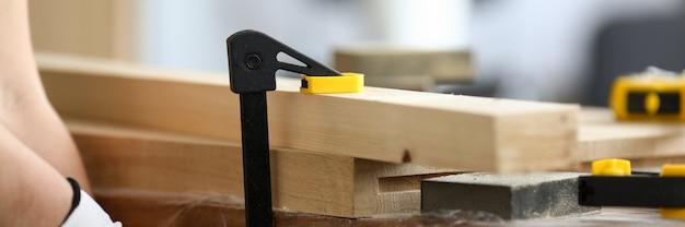 Holzarbeiter befestigt holzteile auf werkbank. vise ist auf der workbench installiert. sorgfältige verarbeitung und veredelung von holzprodukten mit speziellen tischlerwerkzeugen. ändern der form und des aussehens von holz
