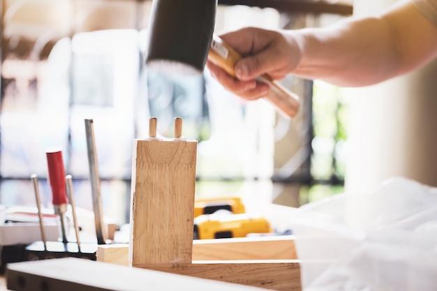 Holzarbeiter hält hammer, um die holzstücke nach kundenwunsch zusammenzubauen