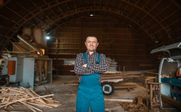 Holzarbeiter in uniform an seinem arbeitsplatz auf holzmühle, holzbearbeitungsmaschine, holzindustrie, zimmerei. holzverarbeitung auf fabrik, waldsägen im holzplatz