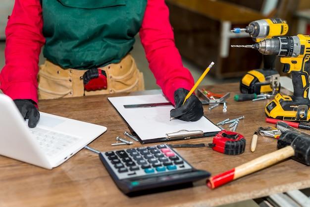 Holzarbeiter machen neues projekt am arbeitsplatz mit laptop