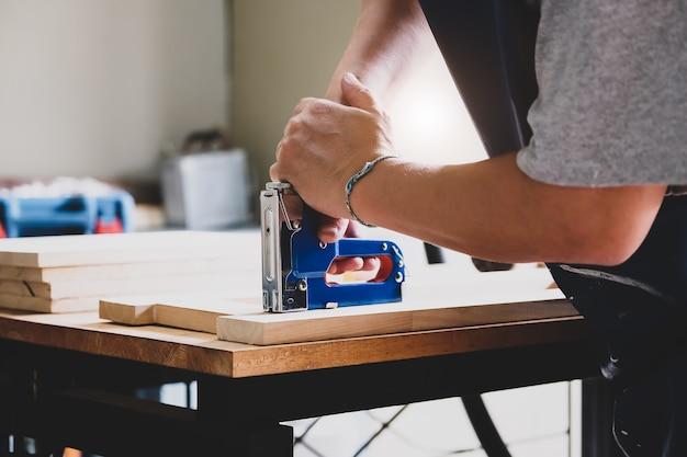 Holzarbeiter mit einem tacker, um die holzstücke nach kundenwunsch zusammenzubauen