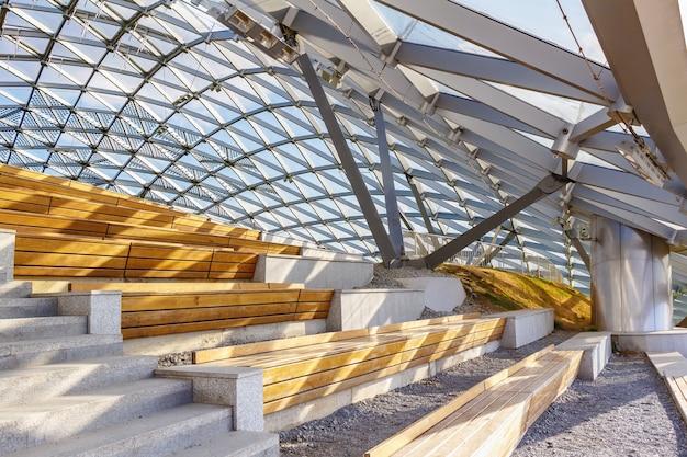Holzbänke unter glasdach im sonnenlicht