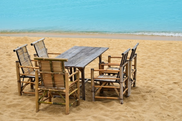 Holzbambusmöbel, tisch und fünf stühle am sandstrand