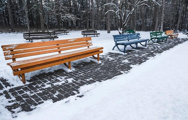 Holzbank im park, mit schnee bedeckt. beginn des winters.