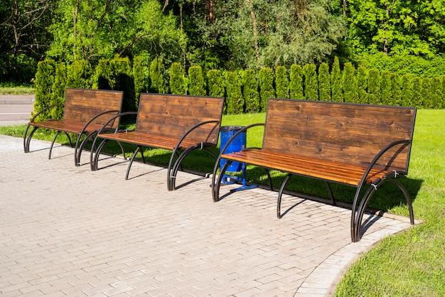 Holzbank mit eisenbeinen in einem park an einem sonnigen tag im sommer