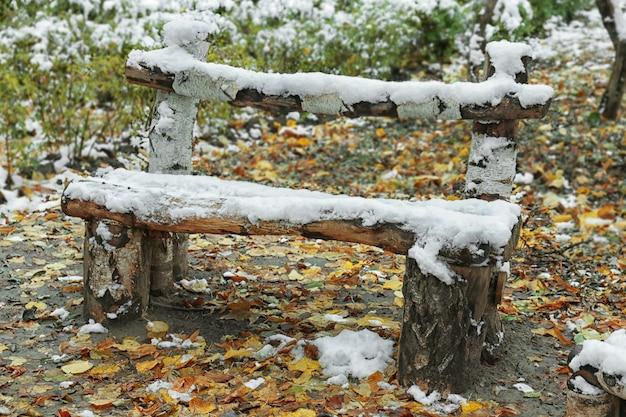 Holzbank mit schnee bedeckt im winterpark