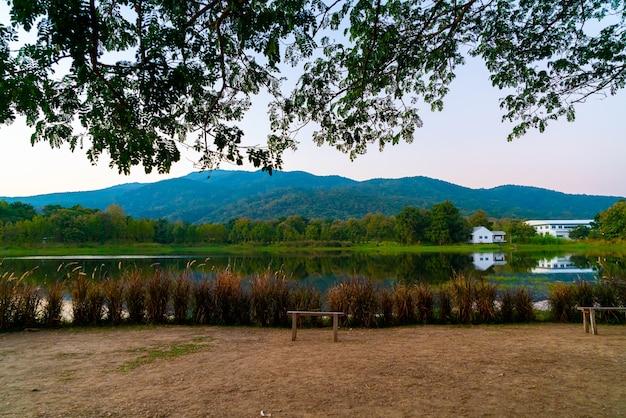 Holzbank mit schönem see in chiang mai mit bewaldeten bergen und dämmerungshimmel in thailand.