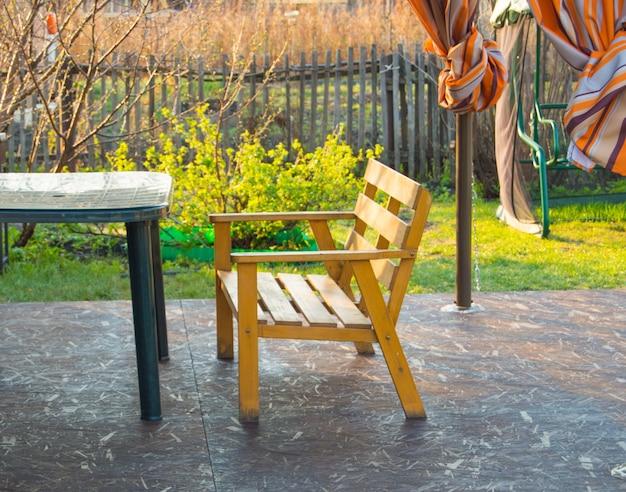Holzbank und grüner plastiktisch auf der veranda in einem landhaus, vorfrühling, im freien