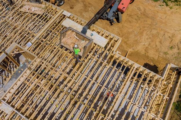 Holzbaurahmen auf neuem wohnbauhaus, das nach hause einen boom-lkw-gabelstapler im neuen zuhause einrahmt