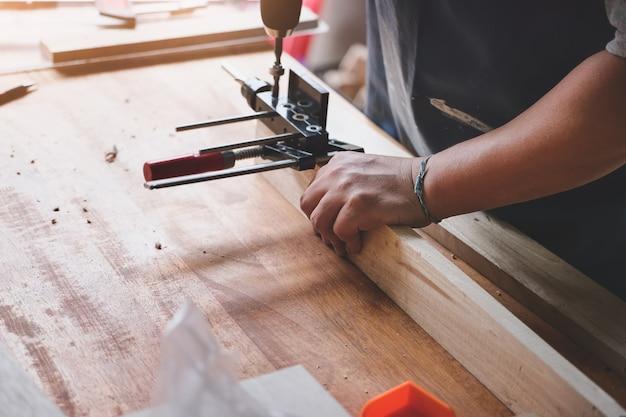 Holzbearbeiter bohren mit einem bohrer löcher in holz, um holztische für kunden zu montieren und zu bauen