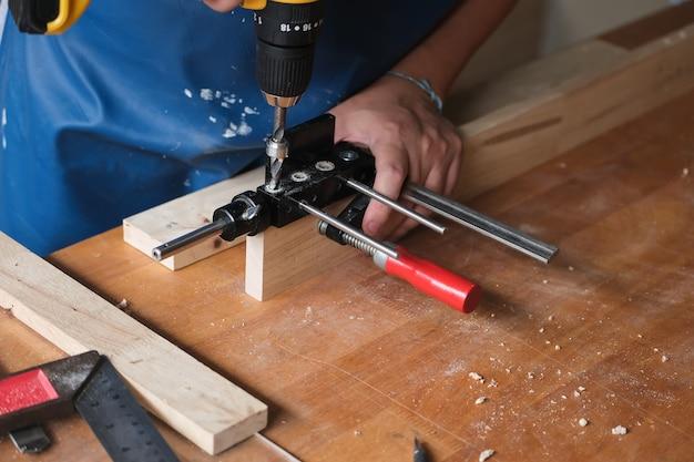 Holzbearbeiter verwenden einen bohrer durch die holzlöcher, um holztische für kunden zusammenzubauen und zu bauen.